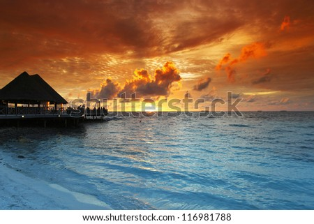 Beach and tropical resort hotel of Maldives on sunset - stock photo