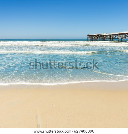 Beach and white sand. The turquoise water of the ocean lagoon. Blue sky. San Diego, USA