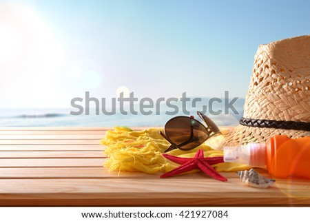 Beach articles on a table wooden slats and sea background with sunbeam. Horizontal composition. Front view. - stock photo