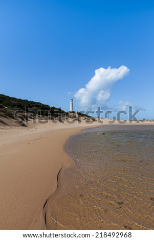 Beach at Lighthouse at Cape Trafalgar along the southern atlantic coast in spain - stock photo