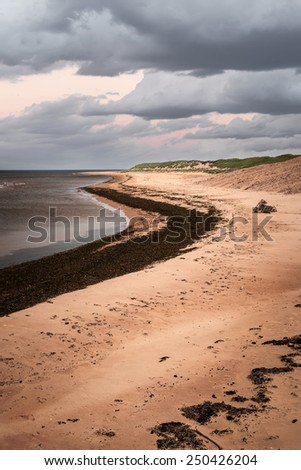 Beach at sunset in Prince Edward Island, Canada with dark cloudy sky - stock photo