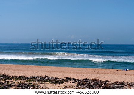 Beach at Umhlanga Rocks with fishing rod and bucket on the beach and ships on the horizon. - stock photo