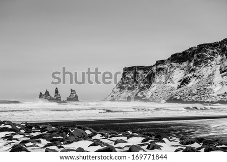 Beach at Vik with a vidm on Dyrholaey in stormy weather - stock photo