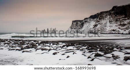 Beach at Vik with a view on Dyrhólaey in stormy weather  - stock photo