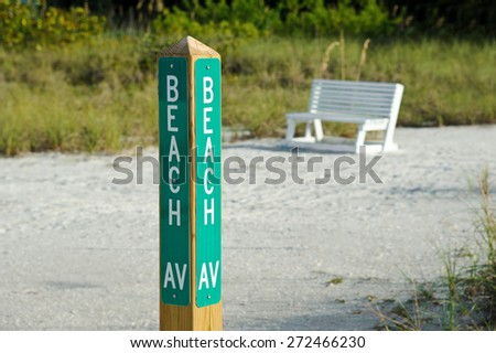 Beach Avenue Sign Post on the Beach marking Public Beach Access Street with a White Park Bench in the Background - stock photo