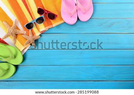 Beach background, wood deck, sunglasses, flip flops, copy space - stock photo