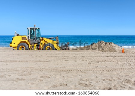 Beach backhoe with pile of sand. Heavy construction equipment vehicle digging sand by the ocean. Orange traffic cone. Clear blue sky, calm water in background. Horizontal photo. - stock photo