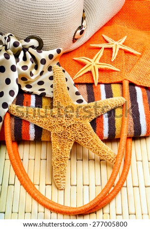 Beach bag and hat with towel and starfish on a wooden background - stock photo