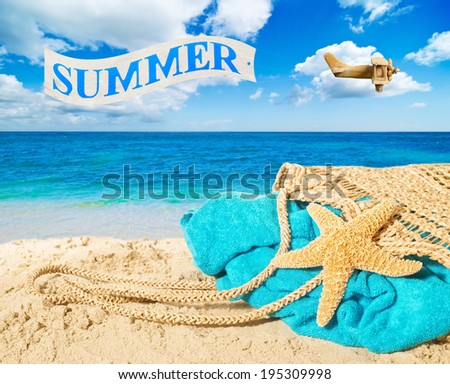 Beach bag and towel with banner over the ocean advertising summer