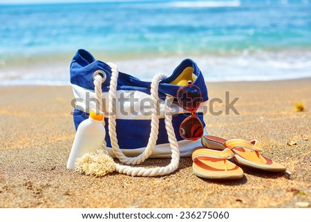 Beach bag, flip flops, sunscreen bottle and sunglasses on a Balinese beach  - stock photo