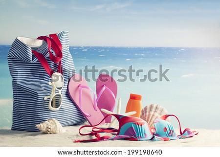beach bag, sun glasses and flip flops on a tropical beach, retro style - stock photo
