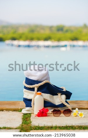 Beach bag, towel, sunscreen and sunglasses near the pool - stock photo