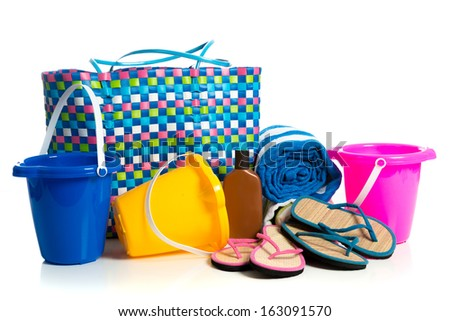 Beach bag with buckets, towel, flip-flops and suntan lotion on a white background - stock photo