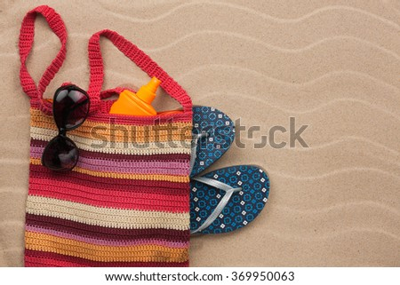 Beach bag with sunscreen, flip flops, sunglasses. Summer holiday background