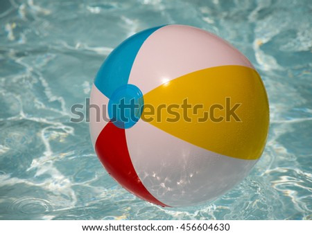 Beach Ball - multicolored inflatable plastic beachball floating on water in pool.