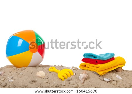 Beach ball with shells, toys and towels - stock photo