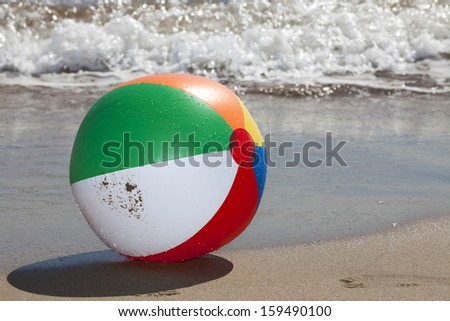 Beach Ball with Water Drops on the Beach with Waves in the Background and Copy Space in right part of image - stock photo