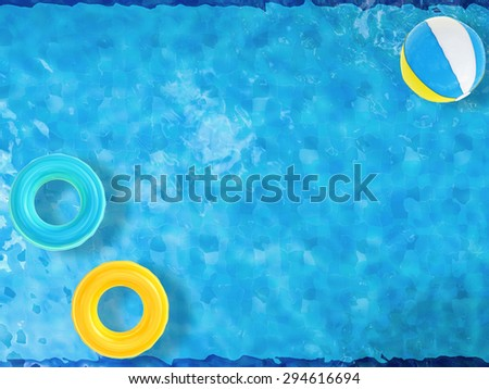 beach balls and swim rings floating on pool top view with blank space