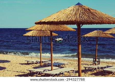 Beach bamboo umbrellas against the sea. Sea summer landscape in vintage tones - stock photo