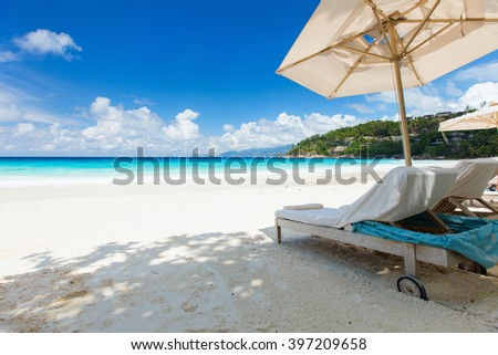 Beach bed and white parasol on perfect tropical white sand beach at luxury resort - stock photo