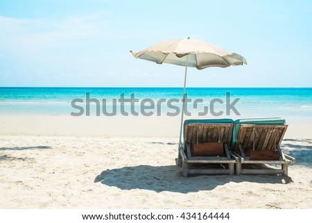 Beach bed with umbrella on white sand beach and beautiful aqua blue sea water - stock photo