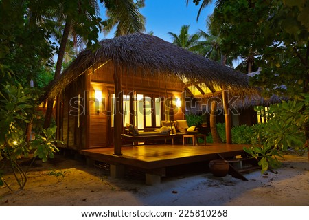 Beach bungalow at sunset - Maldives vacation background - stock photo
