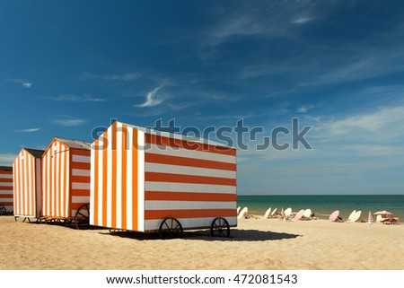 Beach cabins at the North-sea, De Panne, Belgium Red-white striped huts at a sunny beach.