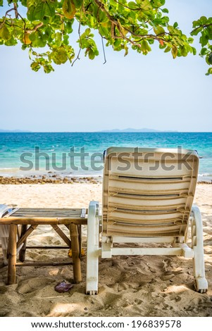 Beach chair and side table are on sand beach