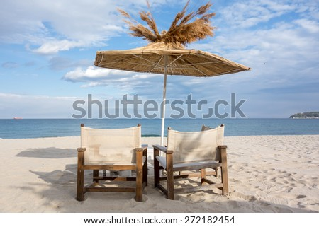 Beach chair and straw umbrella on sand beach with cloudy blue sky - stock photo