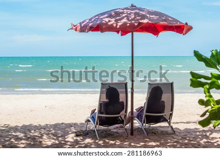 Beach chair and two woman relaxing on a tropical beach.