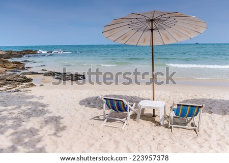 Beach chair and umbrella on sand beach
