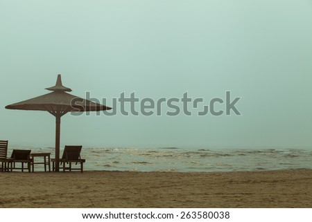 Beach chair and umbrella on sand beach. Concept for rest, relaxation, holidays, resort - stock photo