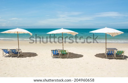 Beach chair and umbrella on sand beach. Concept for rest, relaxation, holidays, spa, resort. - stock photo