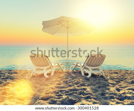 Beach chair and white umbrella on sand beach - stock photo