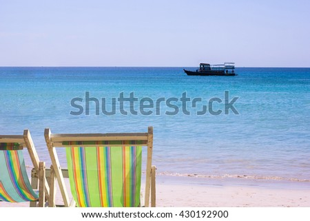 beach chair at blue sea concept : two beach chairs on beach sea with background of  boat on blue sea with sky line : vacation and nature concept