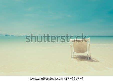 beach chair on beach with blue sky - soft focus with film filter