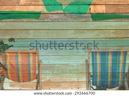 beach chair on sand with blue sea over clear blue sky. on wooden texture background. - stock photo