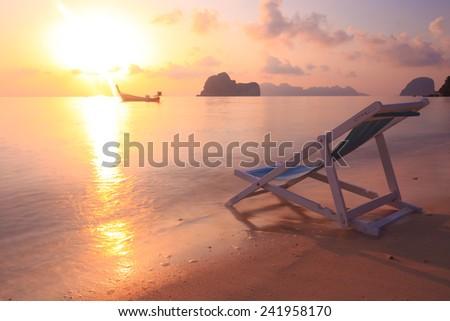 Beach chair on the beach in the sunrise - stock photo