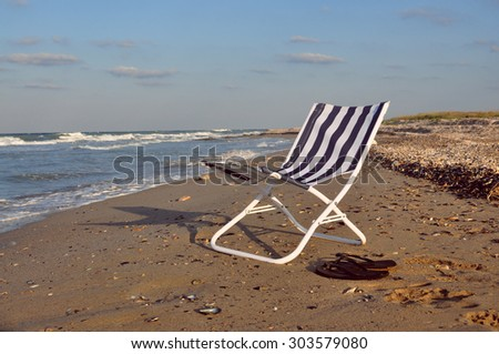 Beach chair on the sea shore - stock photo