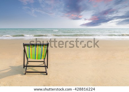Beach chair on the white sand beach with sunset twilight sky and copy space in summer banner for label text or advertisement.