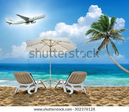Beach chair, palm, airplane and white umbrella. Travel concept - stock photo