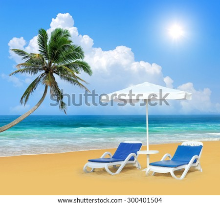 Beach chair, palm, and white umbrella. Travel concept - stock photo