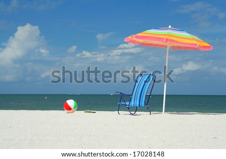 Beach chair, umbrella, flip-flops and ball on a sunny day at the beach