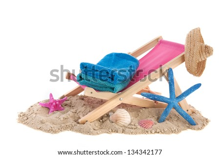 Beach chair with blue towels in the sand