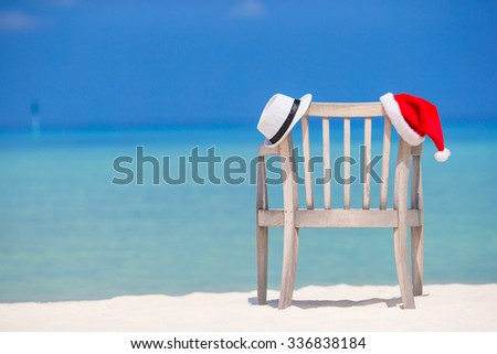 Beach chair with red Santa and straw hat background beautiful turquoise sea  - stock photo