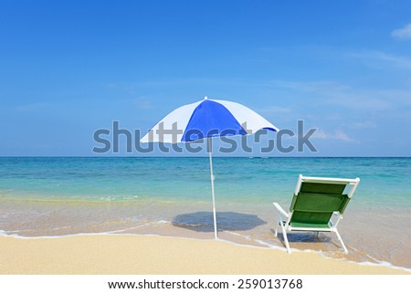 Beach chair with umbrella and beautiful sand beach - stock photo