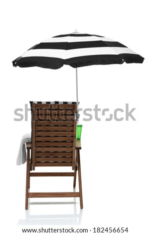 Beach chair with umbrella, towel and drink behind view - stock photo