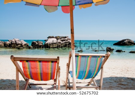 Beach chair with umbrella with view of sea and rocks