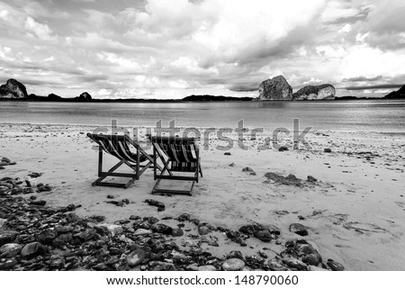 Beach chairs and beautiful beach on black and white tone - stock photo