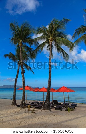 Beach chairs and palms on perfect tropical white sand beach - stock photo